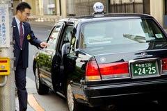 Японские бизнесмены вызывают такси для работы в утре Стоковые Изображения