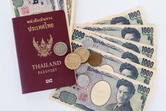японские бумажные деньги и монетка иен валюты с пасспортом на белизне Стоковое фото RF