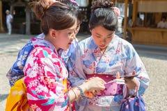 Японские женщины в бумаге удачи чтения yugata стоковая фотография