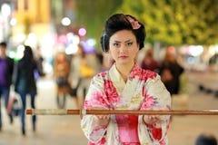 Японские самураи гейши с шпагой снаружи на ноче стоковые изображения