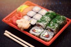 Японские суши в красном пластмасовом контейнере для еды нося на черноте Крен сделанный из мяса краба, авокадоа, огурца внутреннег Стоковое Фото