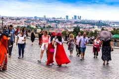 Японские туристы девушек в красных одеждах делают selfie около замка Праги, теперь официальной резиденции президента чехии Стоковые Изображения RF