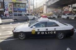 Японские люди полицейскиев управляя автомобилем полисмена на дороге движения идут к Стоковое Фото