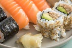 Японский авокадо тунца внутри - вне Калифорния с семгами Nigiri и Maki на плите смешивания суш стоковые фотографии rf