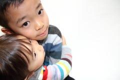 Японский брат и сестра обнимая один другого Стоковые Изображения