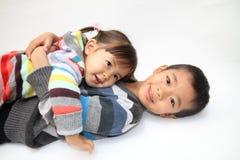 Японский брат и сестра обнимая один другого Стоковая Фотография RF