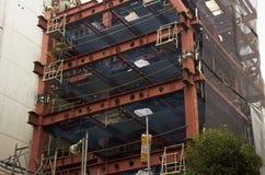 Японский народ работая и башня строения на строительной площадке на Стоковая Фотография