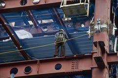 Японский народ работая и башня строения на строительной площадке на Стоковое Изображение
