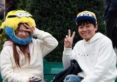 Японский подросток девушки и мальчика в аксессуарах миньона на студиях Universal Японии Миньоны многочисленные выдуманные твари стоковая фотография rf