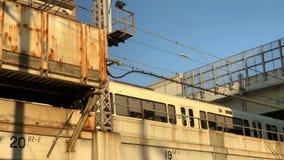 Японский поезд пересекает ржавые мост и дорогу выше на заход солнца в Японии видеоматериал