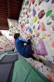 Японский человек взбираясь стена утеса крытая Стоковое Фото
