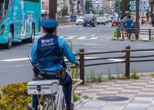 Японское полицейский на велосипеде в улицах токио - ТОКИО, ЯПОНИИ - 12-ое июня 2018 стоковое фото rf