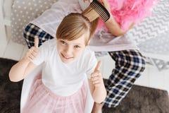 Яркая выведенная девушка имея ее волосы быть введенным в моду папой Стоковые Фото