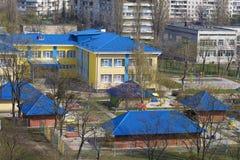 Яркая голубая крыша детского сада на фоне серых городских многоэтажных зданий Стоковое Фото