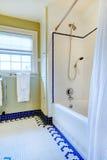 Яркая желтая и белая ванная комната с голубым плиточным полом стоковое фото rf