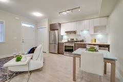 Яркая живущая комната с кухней и обеденным столом Стоковое Изображение RF