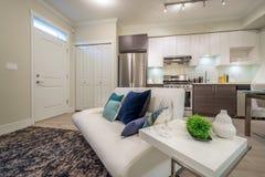 Яркая живущая комната с софой и кухней на заднем плане Стоковые Фотографии RF