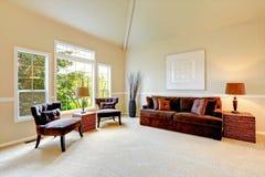 Яркая живущая комната цвета слоновой кости с высоким сводчатым потолком и французскими wi Стоковые Фотографии RF