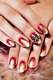 Яркая заполированность красного цвета и золота на ногтях Стоковые Фото