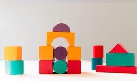 Яркая красочная деревянная игрушка блоков Дети кирпичей строя башню, замок, дом стоковые фотографии rf