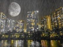 Яркая луна светя над городом рекой в дожде Стоковые Фото