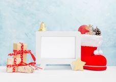 Яркая насмешка рождества вверх с белой горизонтальной рамкой фото: праздничные подарочные коробки, игрушки, и ель-конусы в красно Стоковое Изображение