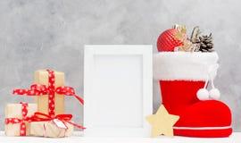 Яркая насмешка рождества вверх с рамкой фото: праздничные подарочные коробки, игрушки, и ель-конусы в красном ` s santa boot конц Стоковые Фото
