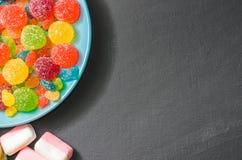 Яркая покрашенная конфета, конфета, зефир, помадки на темной предпосылке на голубой плите Стоковая Фотография RF