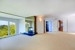 Яркая пустая комната с камином и стеклянной стеной Стоковое фото RF