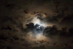 Яркая луна в темном небе peeking вокруг тучных облаков Стоковая Фотография
