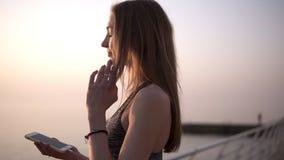 Яркая, худенькая девушка стоит в утре около моря, кладет дальше наушники, мобильный телефон в ее руках подготовлять видеоматериал