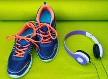 Яркие ботинки и наушники на свернутой циновке йоги Стоковые Фото