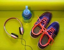Яркие ботинки, наушники и бутылка с водой на свернутой циновке йоги Стоковое фото RF