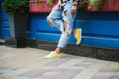 Яркие желтые тапки и джинсы Стоковые Изображения