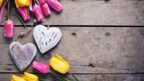 Яркие желтые и розовые тюльпаны весны и 2 декоративных сердца Стоковая Фотография RF