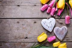 Яркие желтые и розовые тюльпаны весны и 2 декоративных сердца Стоковые Изображения