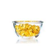 Яркие желтые мягкие пилюльки геля в ясном стеклянном шаре Стоковые Фотографии RF