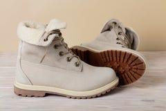 Яркие кожаные ботинки зимы на светлой деревянной предпосылке Стоковая Фотография RF