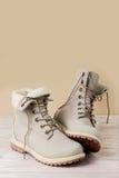 Яркие кожаные ботинки зимы на светлой деревянной предпосылке Стоковые Фотографии RF