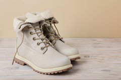 Яркие кожаные ботинки зимы на светлой деревянной предпосылке Стоковая Фотография