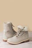 Яркие кожаные ботинки зимы на светлой деревянной предпосылке Стоковое Изображение RF