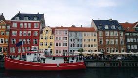 Яркие красивые фасады зданий на портовом районе Nyhavn и красно-белого корабля на воде Стоковое Фото