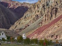 Яркие красные горы, слои утесов чередуют друг с другом, в предгорьях холмов белые буддийские stupas, Ladakh, Nort Стоковое фото RF