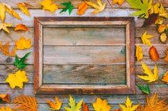 Яркие листья осени и картинная рамка на деревянной предпосылке с космосом экземпляра глумитесь вверх для текста, поздравлений, фр Стоковое фото RF