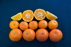 Яркие мандарины гармонично лежат на синей предпосылке Куски цитруса и корки стоковые фотографии rf