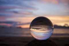 Яркие облака захода солнца над океаном отраженным в стеклянном шарике Стоковые Изображения RF