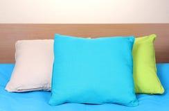 Яркие подушки на кровати Стоковые Изображения