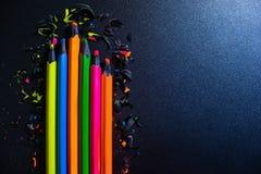 Яркие покрашенные карандаши и shavings от карандашей на темной предпосылке стоковое изображение rf