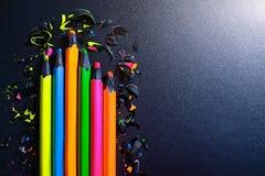 Яркие покрашенные карандаши и shavings от карандашей на темной предпосылке стоковые фото