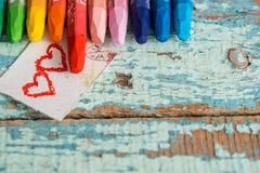 Яркие покрашенные карандаши на старой предпосылке голубого зеленого цвета деревянной 2 красных сердца покрашенного на куске бумаг Стоковая Фотография RF